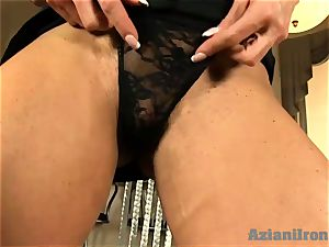 Buff lady slides black dildo in her moist cunt